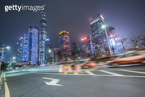 blurred road and modern office buildings at night