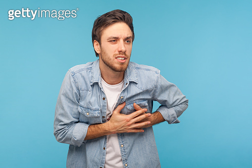 Cardiac problems. Portrait of stressed out, worried man in denim shirt clutching chest, suffering heart attack