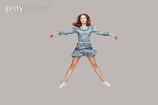 Full length girl vintage ruffle dress levitating hovering in mid-air, spread hands legs like a star, jumping trampoline