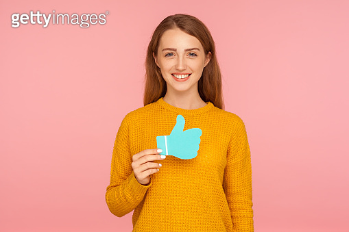 Like and share! Portrait of beautiful happy red hair girl in sweater holding blue thumb up love icon and smiling