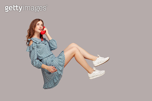 Charming girl in ruffle dress holding phone handset levitating, hovering floating air and having conversation