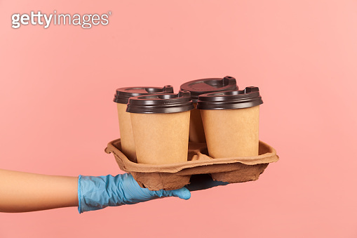 Profile side view closeup of human hand in blue surgical gloves holding and showing cups of hot takeaway mug drink in hand