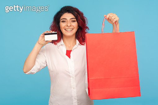 Bank loan for purchase. Portrait of woman with fancy red hair holding shopping bags and credit card