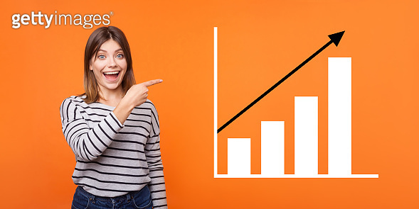 Portrait of amazed happy joyful young woman standing, pointing aside and showing business growth graph.