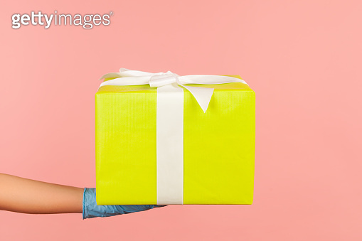 Profile side view closeup of human hand in blue surgical gloves holding gift box. sharing, giving or delivery concept.