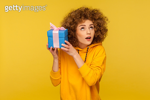 Portrait of funny curious woman in urban style hoodie holding present box near ear and listening what's inside