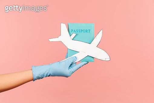 Profile side view closeup of human hand in blue surgical gloves holding passport and airplane paper.