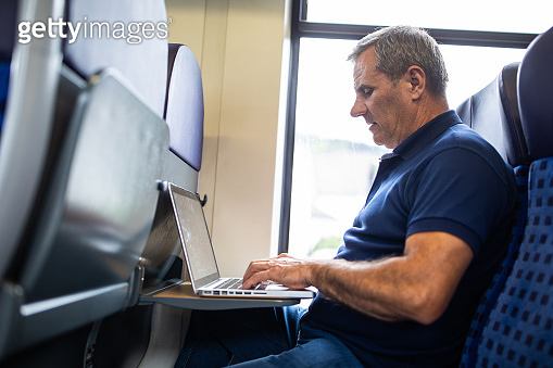 Mature businessman using laptop while traveling by passenger train