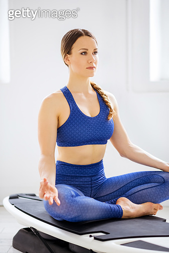 Young woman doing a surf yoga lotus pose