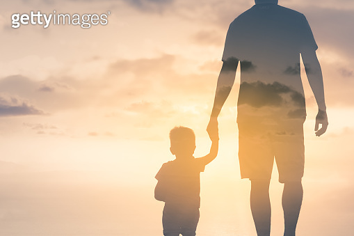 Father and son holding hands walking into the golden sunset.
