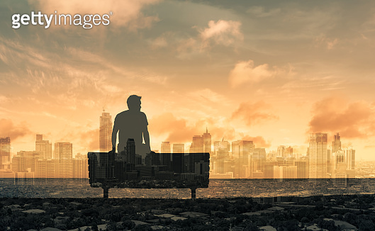 Thoughtful young man sitting on the bench and looking at the city skyline.
