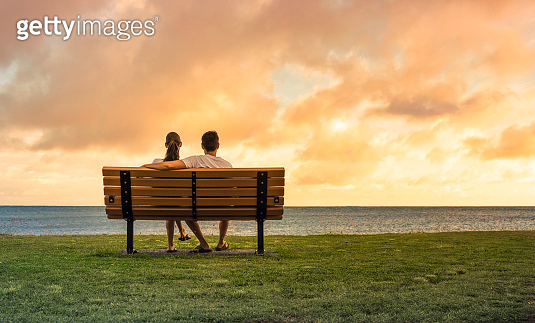 Young couple relaxing on park bench at sunset.
