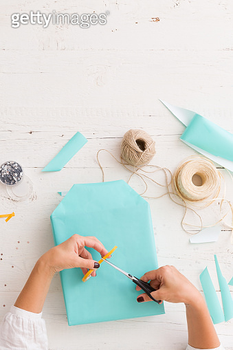 Top view on gift wrapping. The girl packs a gift in a paper of turquoise color. Gift ribbons, twine, scissors and gift on a white wooden table. Preparation for the holiday. Christmas, birthday, etc.