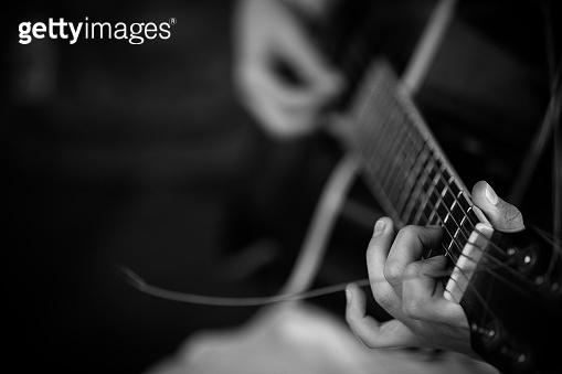 Closeup of musician's hands playing guitar at a concert.