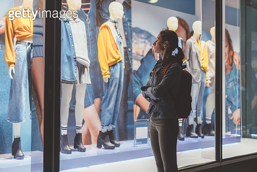 Girl stands outside the store and looks at the female clothes on the mannequins.