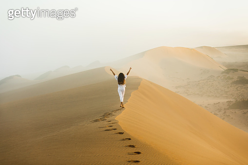 Woman walking on top of huge sand dune in Morocco Sahara desert. Beautiful warm sun light and mist in morning. View from behind. Freedom concept.