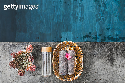 Two gray hand towels in wicker basket and Glass reusable water bottle on poolside in hotel spa. Pink lilavadi flower as decoration. Beauty treatment.