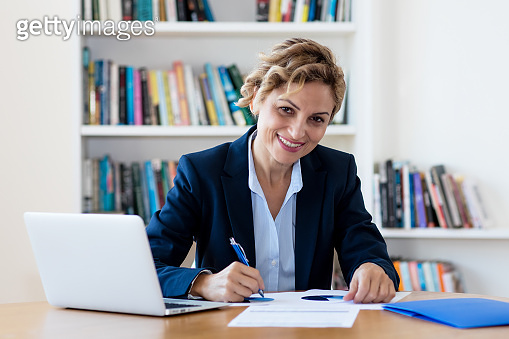 Laughing mature adult businesswoman working at desk