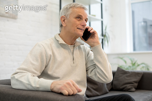 Smiling older man using mobile phone at home