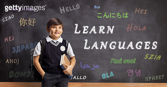 Schoolboy in front of a blackboard with hello written in different languages and text learn languages