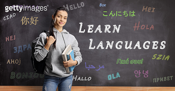 Female student standing in front of a blackboard with hello written in different languages