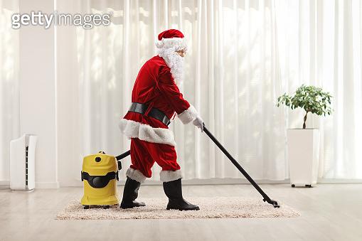 Santa claus using a vacuum cleaner