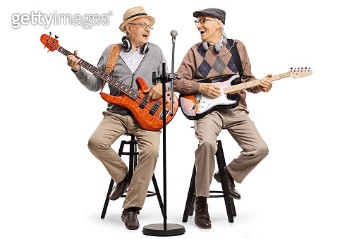 Cheerful elderly men sitting on chairs playing guitars and singing