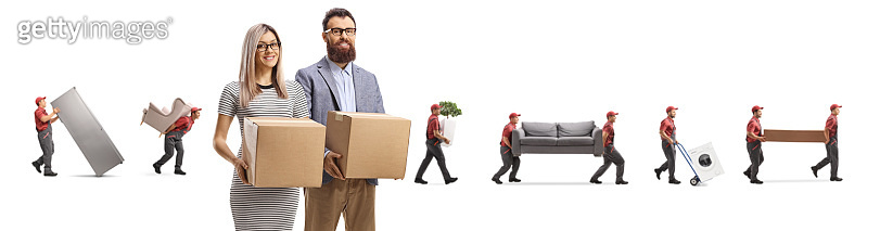 Husband and wife holding cardboard boxes and movers carrying household items behind