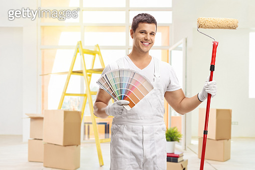 House painter with a color swatch and a paint roller in a house
