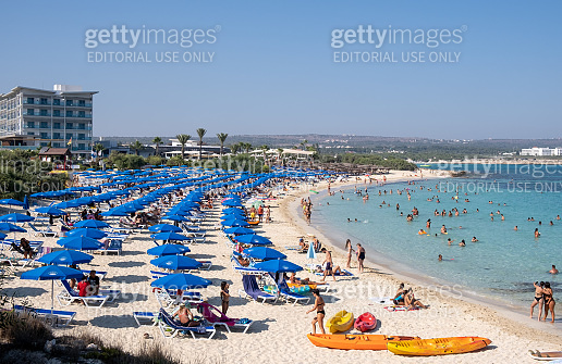 Idyllic beach with golden sand and turquoise water with tourists in summer