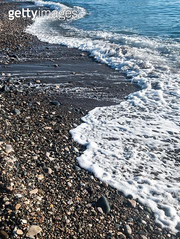 Sea waves splashing to a pebble beach