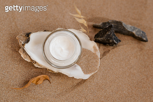 Caring cosmetics in an oyster shell on the sand. Eco-friendly organic cosmetics.