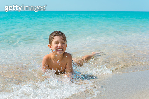 A cheerful kid on the beach lies in the clear sea water.