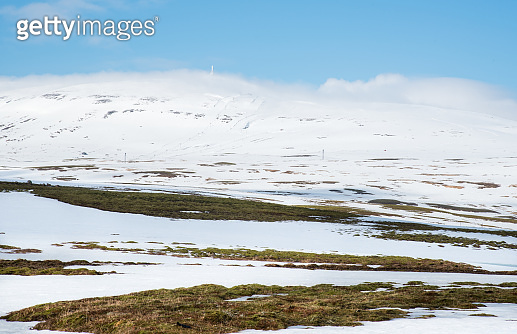 Icelandic landscape with mountains and meadow covered in snow and ice in Iceland
