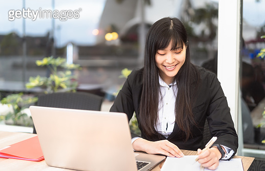 Business Asian woman working on computer outdoor - Happy Chinese girl using laptop in office - Professional job and people lifestyle technology concept