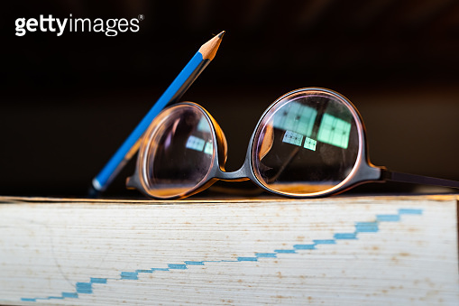 Glasses and pencil on a dictionary