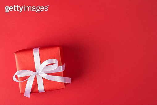 happy holidays concept. Above overhead close up view photo of packed gift box with white ribbon isolated bright color red background