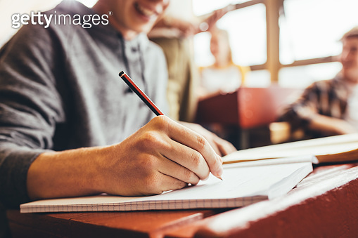 Student taking notes sitting at desk during lecture