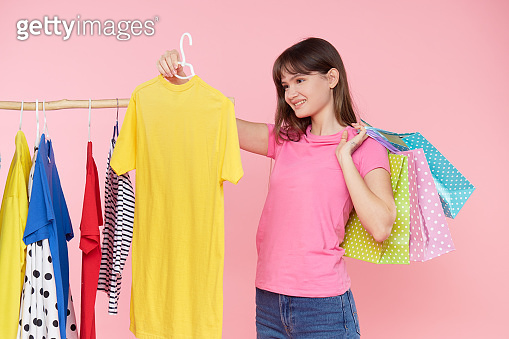 Online shopping. Young asian woman with shopping bags tries on colorful fashion clothes in the store. Pink background