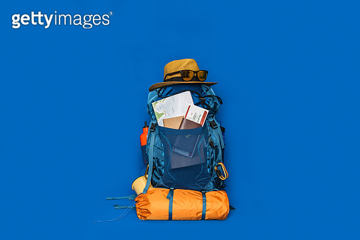 Tourist planning vacation with the help of world map with other travel accessories around. concept Luggage with accessory for travelers Vacation on Blue color background. Travel backpack