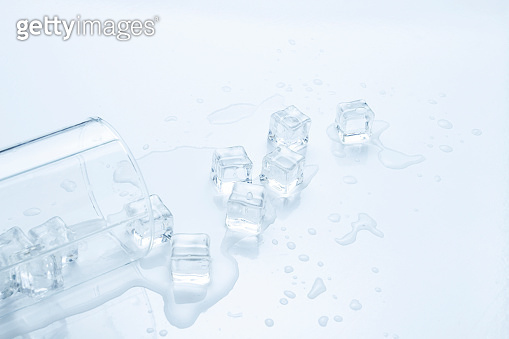 Spilled glass of water with ice on a light background