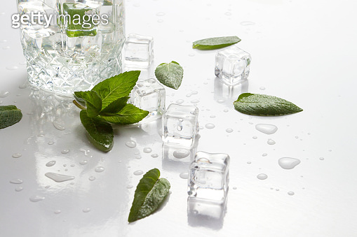 Glass with refreshing water, mint leaves, water droplets and ice