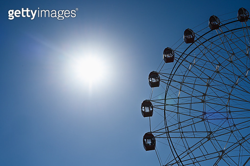 ferris wheel on a background of sky and sun. Ferris wheel on sky background. Ferris wheel on sunny sky background