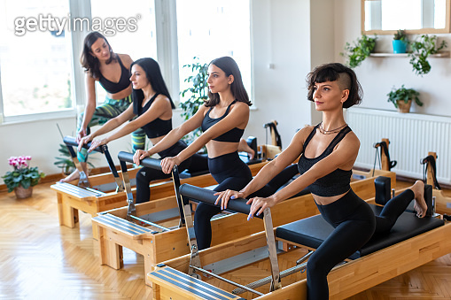 Women Doing Exercises on Pilates Reformer Bed with Female  Instructor at Gym