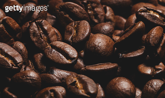 Brown roasted beans of arabica coffee. Dark background
