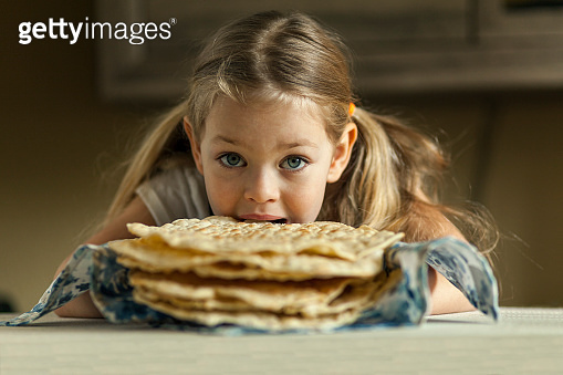 While mom does not see. Beautiful little girl bites off a piece of fresh smelling pita bread. Armenian flat bread (lavash)