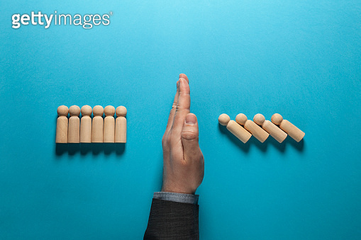 Hand of businessman in suit stops falling figures of people (employees), domino effect. Finance crisis and risk, solution of danger problem. Economic strategy of success