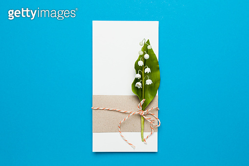 Congratulation and invitation to the holiday. Lily of the valley flowers and a note on a blue background