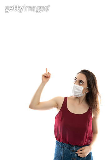 Portrait of a young woman wearing a mask against a white studio background