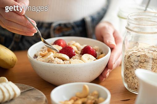 Woman eating oatmeal porridge with fruits